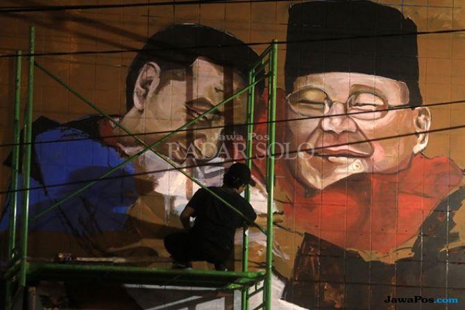 Jokowi-Prabowo Berpelukan Jadi Objek Seniman Mural